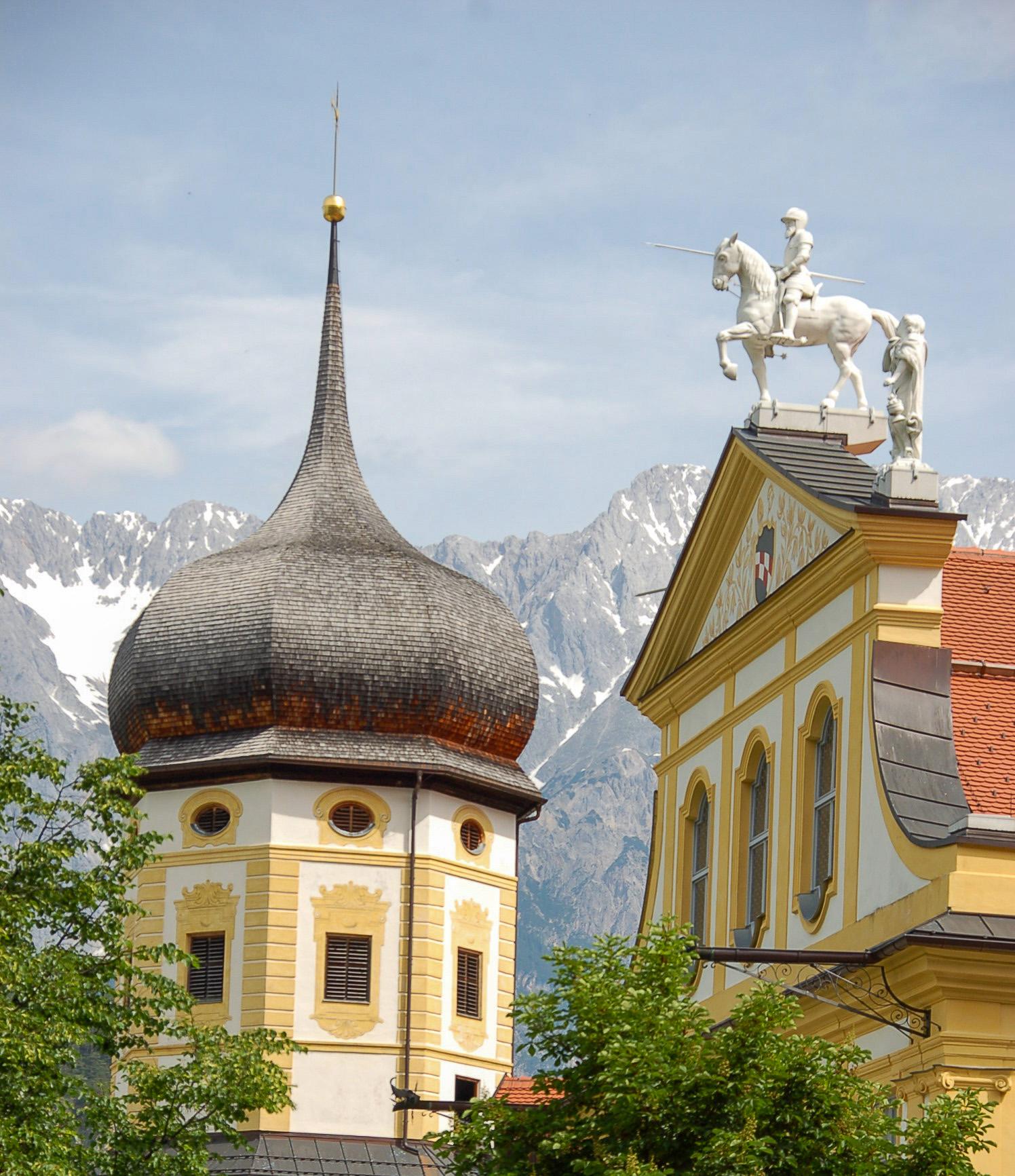 Der Stift in Stams mit Zwiebelturm und Reiterdenkmal vor den Alpen
