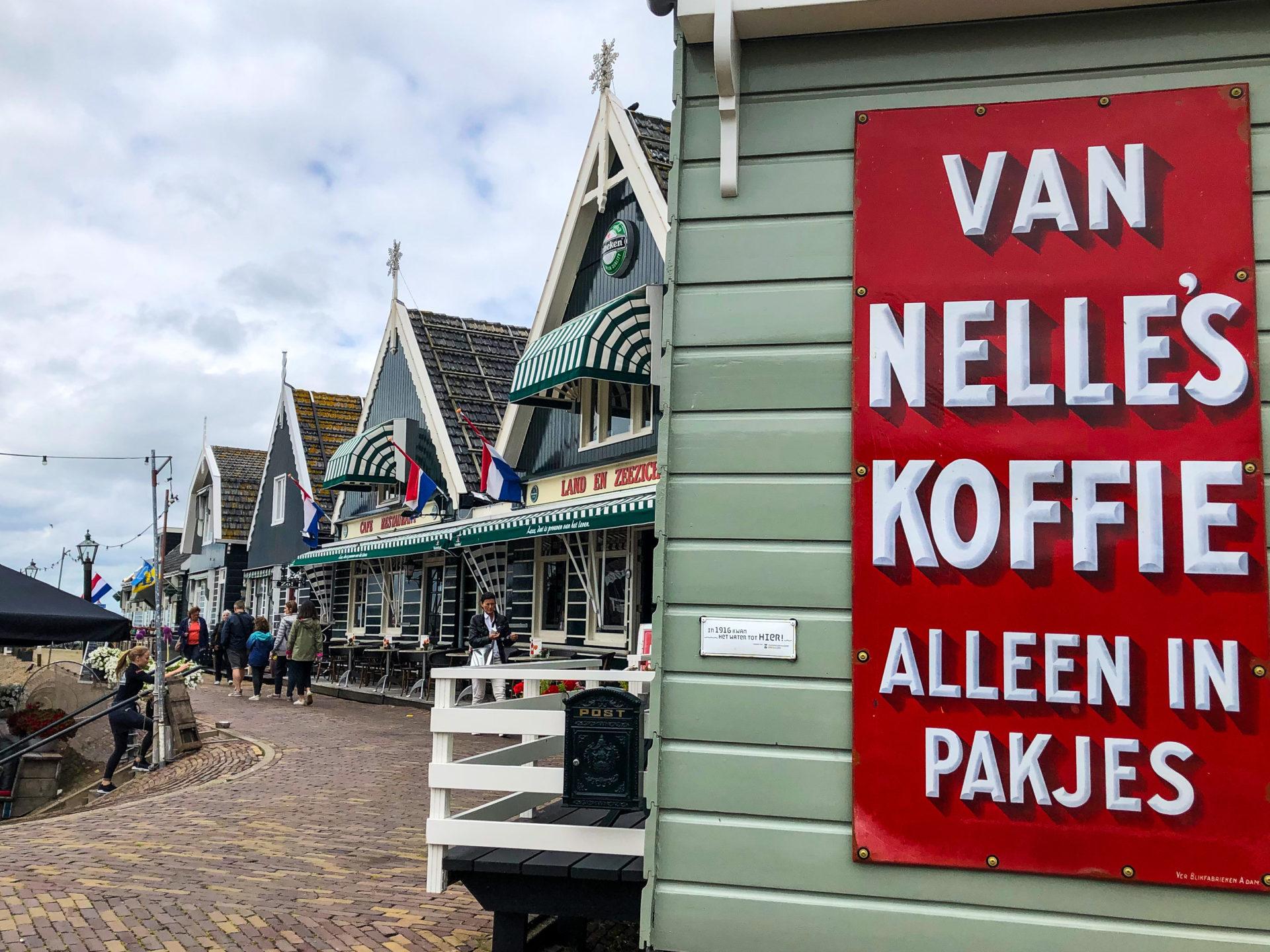 Kaffeewerbung an einem Holzhaus im Hafen von Marken