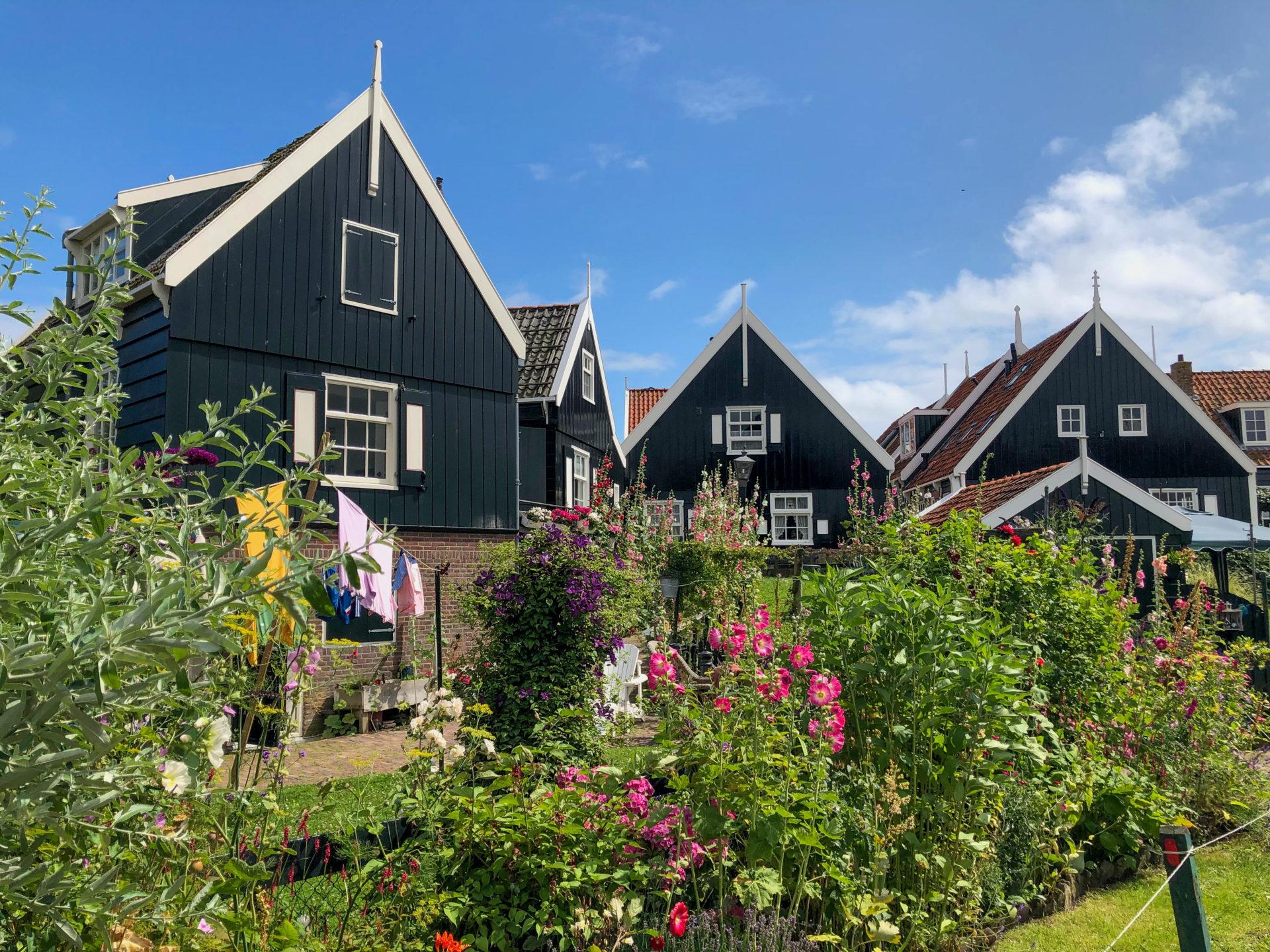 Holzhäuser mit Blumen in Marken bei Sonne