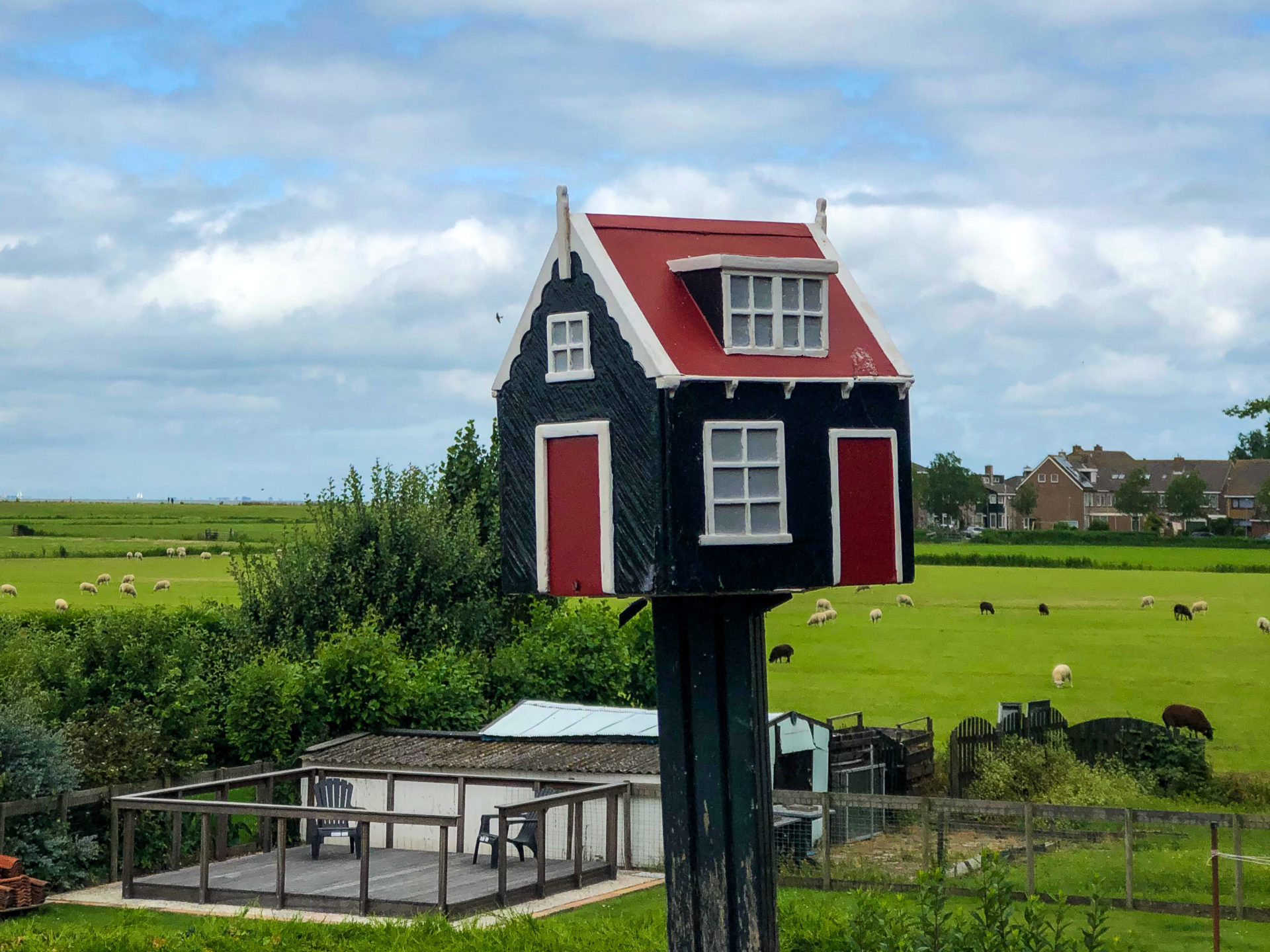 Modellhaus in einem Garten im holländischen Marken mit Kuhweide im Hintergrund
