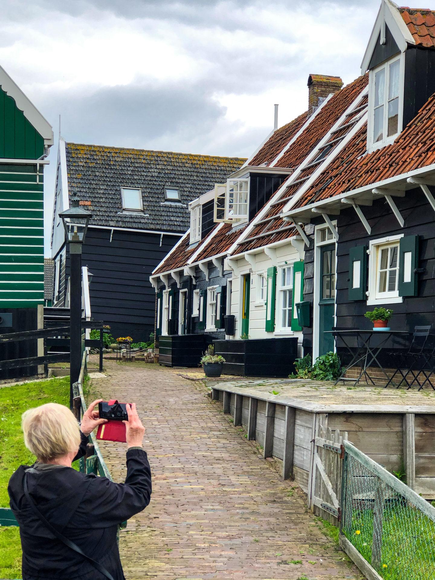 Touristin fotografiert Holzhäuser in Marken in Holland