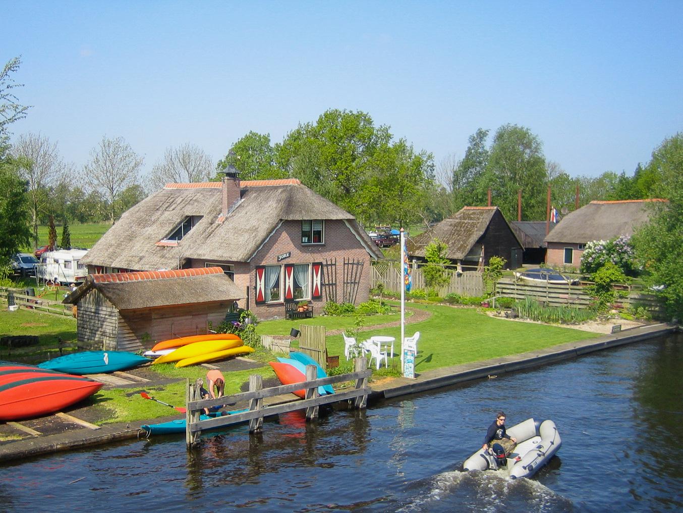Motorboot und Kanus vor Haus mit Reetdach vor der Bootstour in Giethoorn