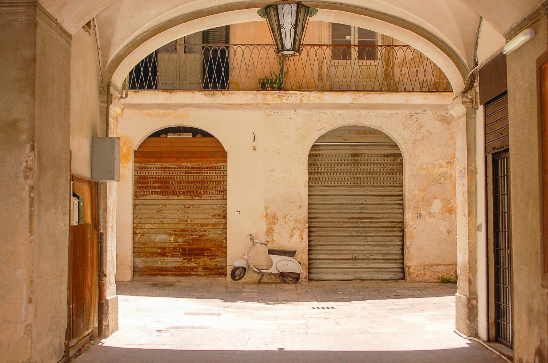 Häuser mit Arkaden und Vespa in der süditalienischen Stadt Lecce