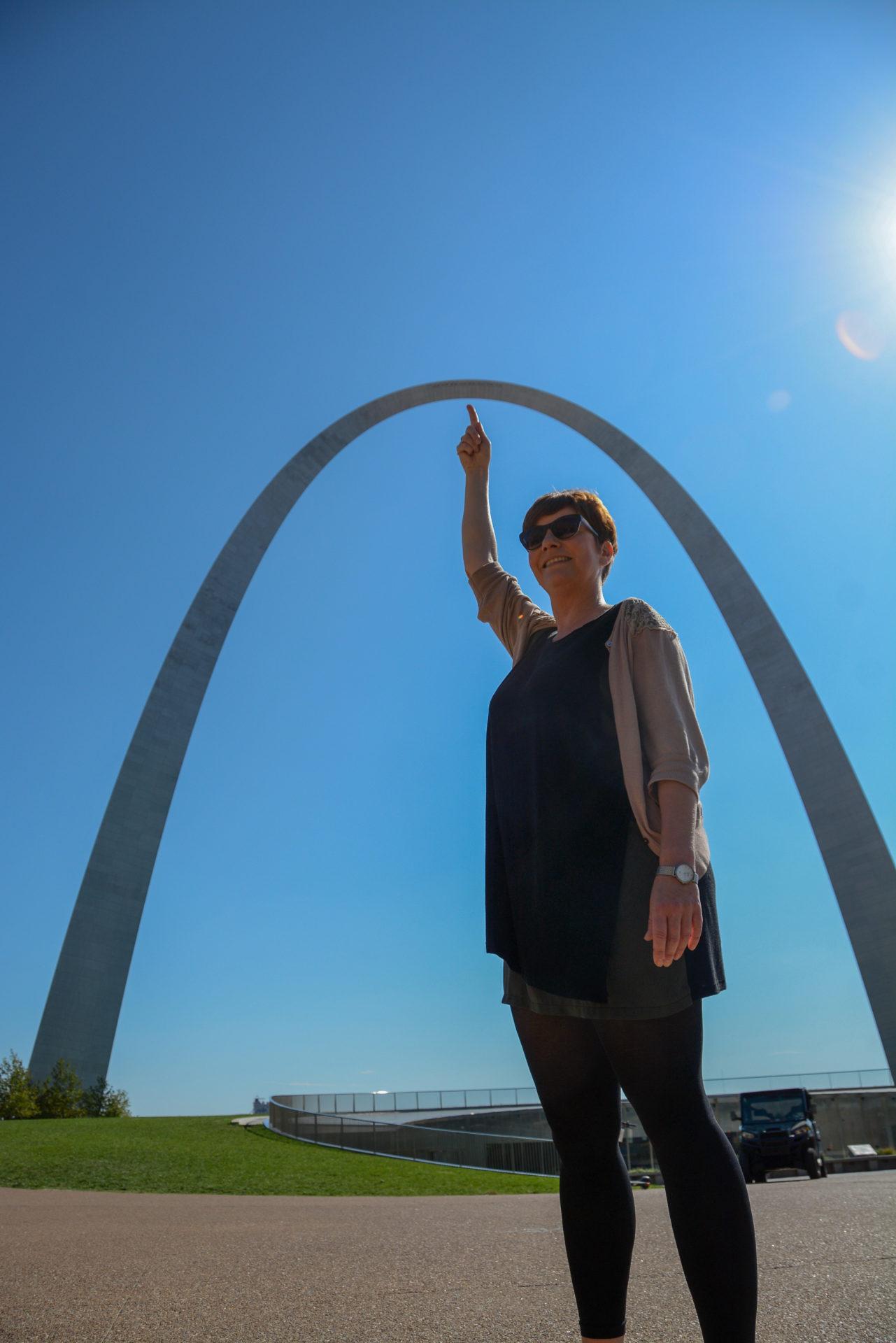 Junge Frau deutet mit dem Finger auf den Gateway Arch in Saint Louis