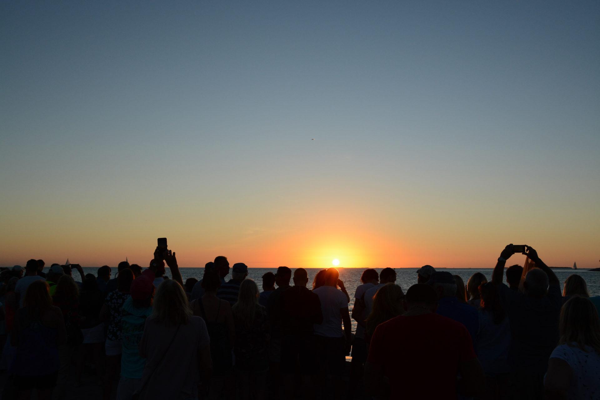 Menschenmenge in Key West feiert den Sonnenuntergang mit Anekdoten über Hemingway und Havanna