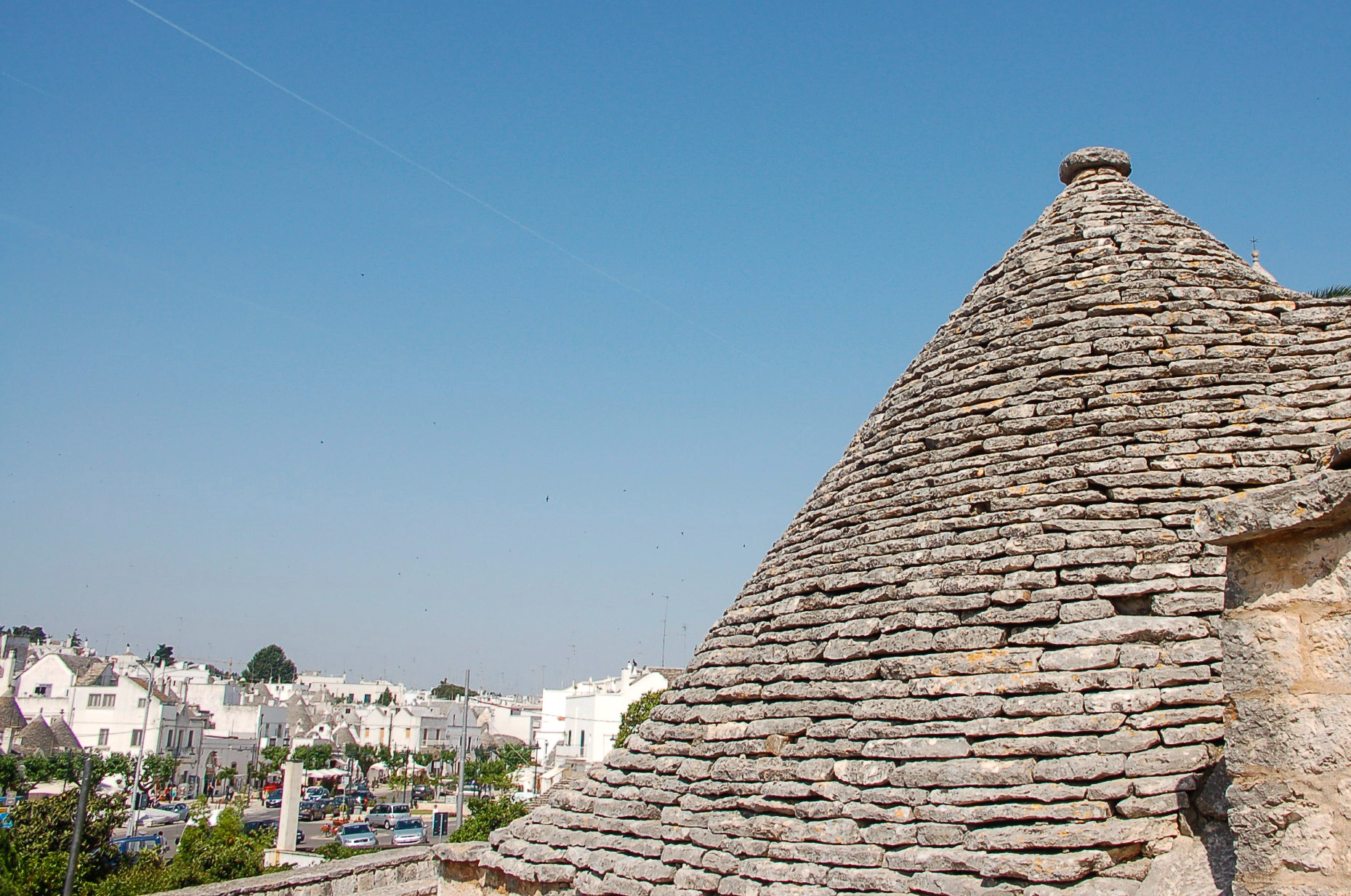 Das Dach eines Trullo in Alberobello mit Stadtansicht und Chemtrails am Himmel