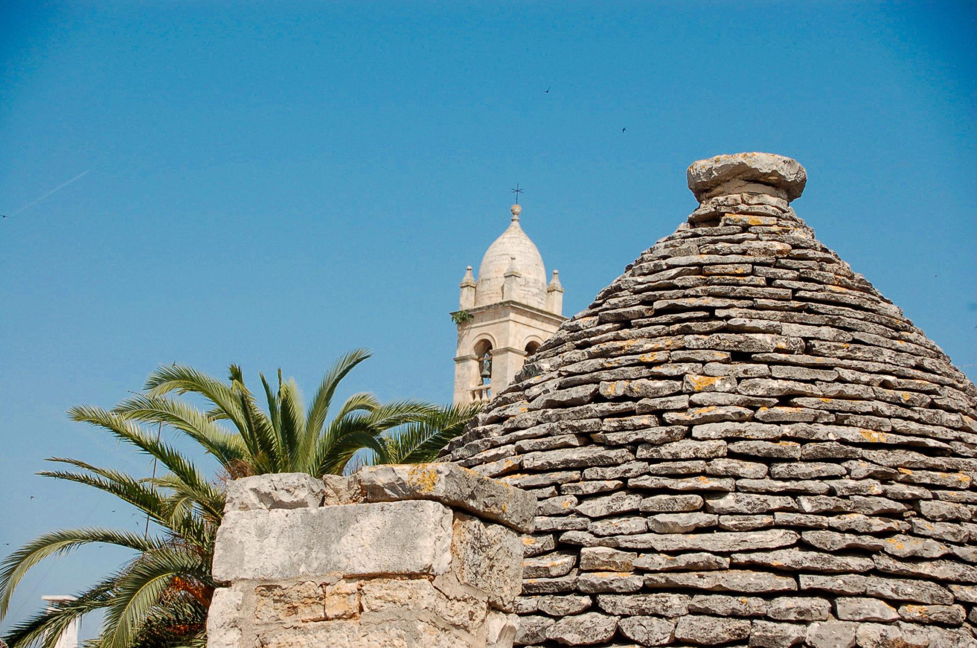Ein Trullo in Alberobello mit dem Turm der Kirche und einer Palme