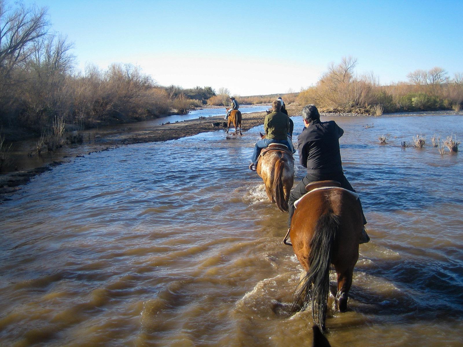 Reiter auf Pferderücken durchqueren einen Fluss in Scottsdale