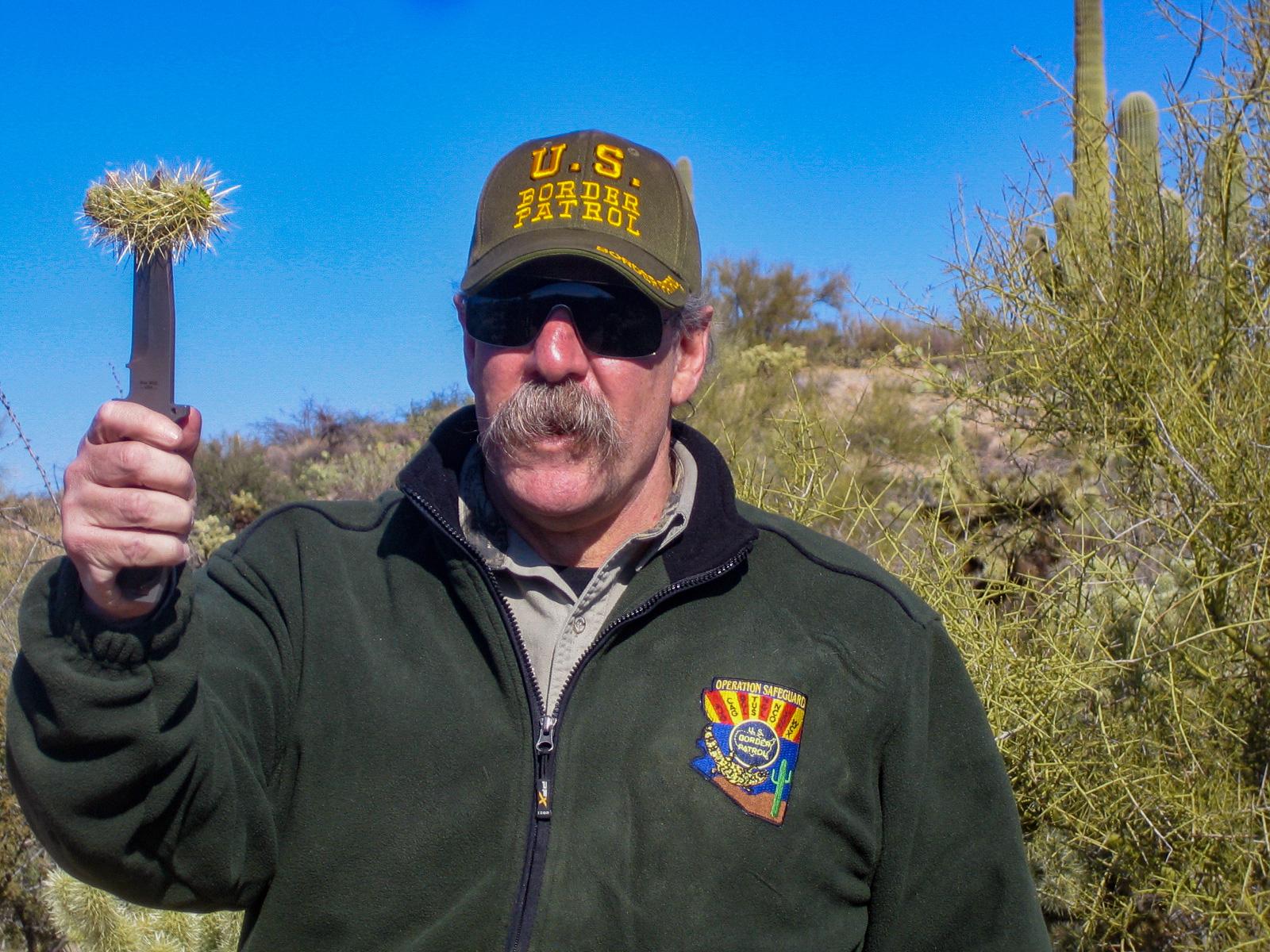 Ein Mann mit einem Messer und einem Stück Kaktus im Ornat der US Border Patrol