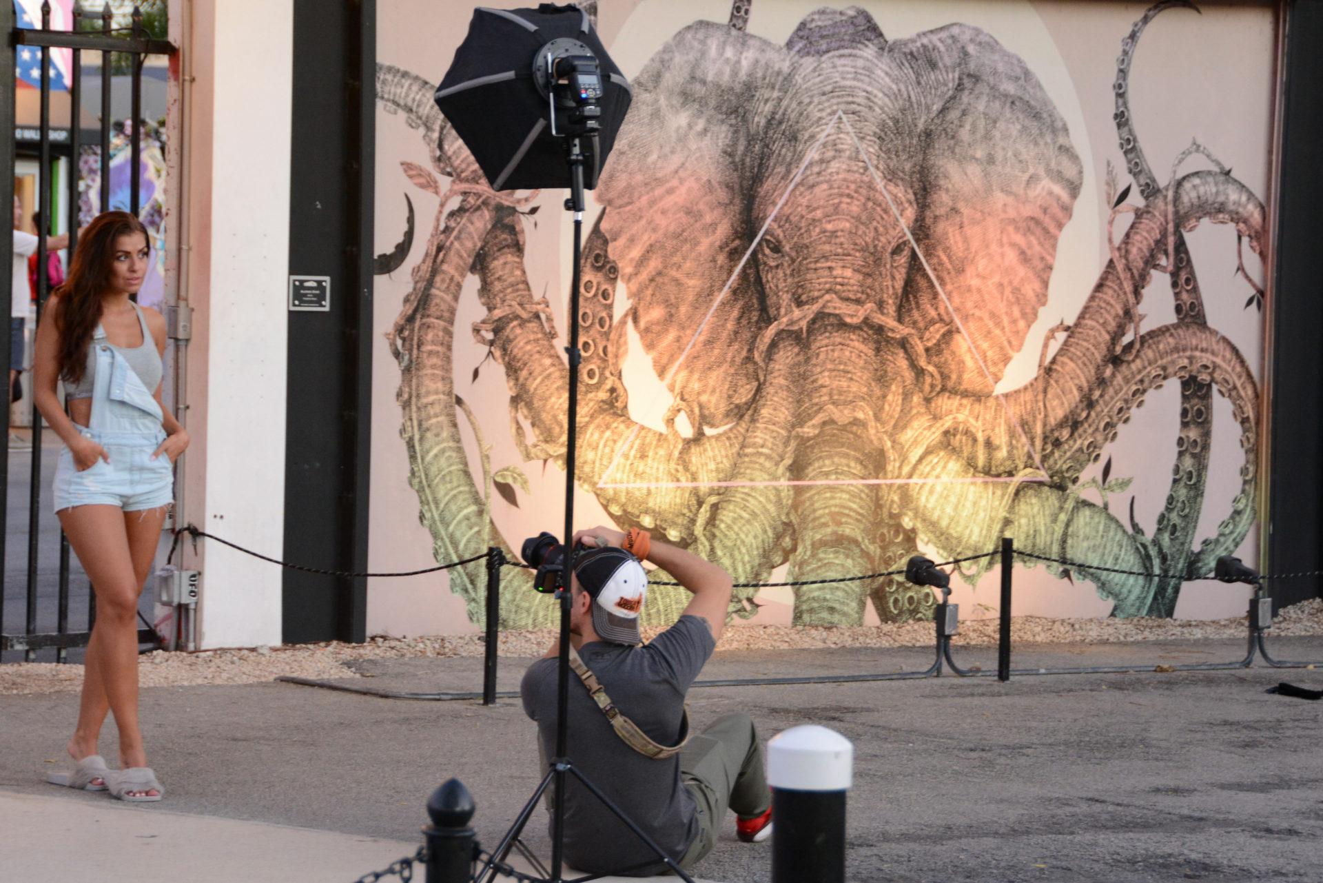 Model wird fotografiert in Wynwwod, Miami, mit Mural von Elefant mit Oktopusarmen