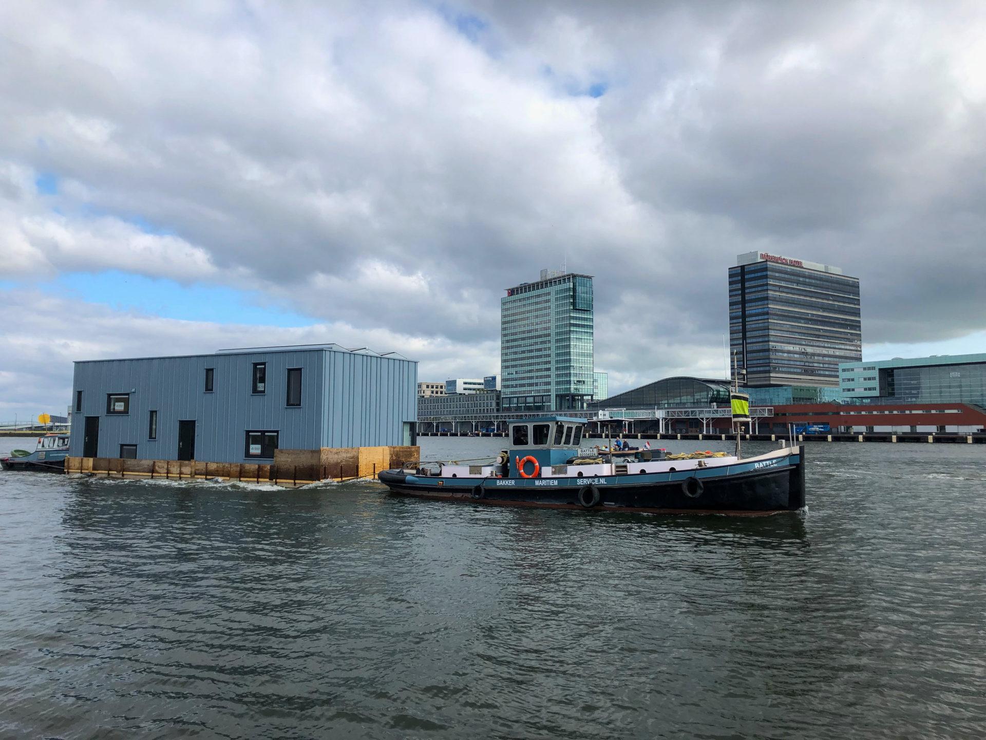 Ein Schlepper zieht ein Hausboot über das IJ in Amsterdam Noord