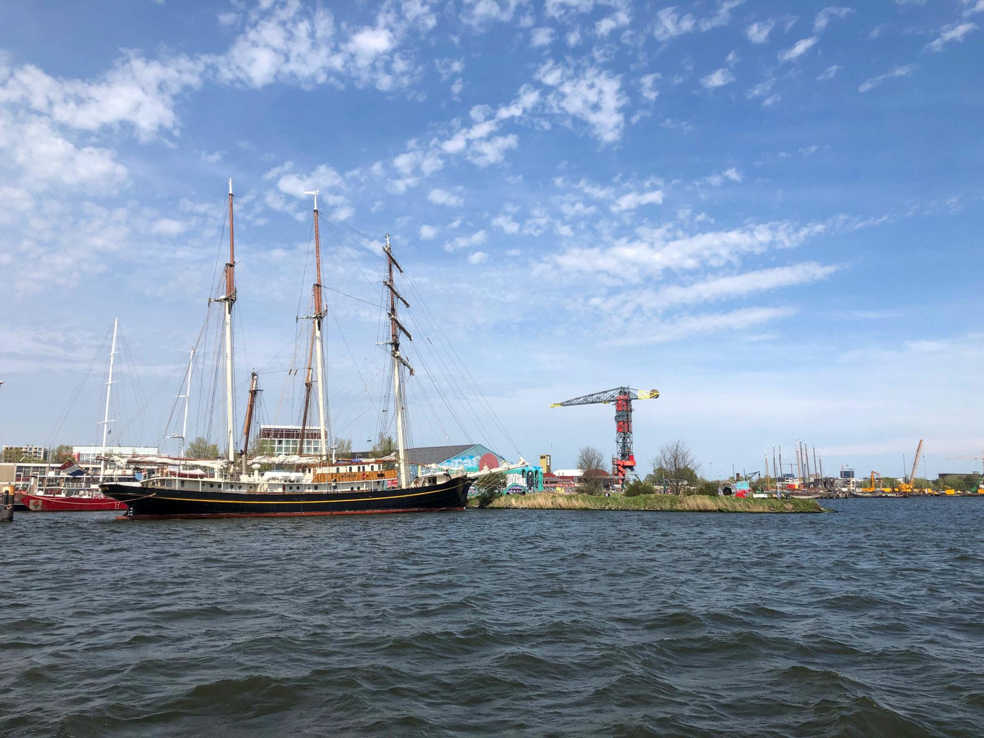 Segelboot vor hafenkran an der NDSM-Werft in Amsterdam