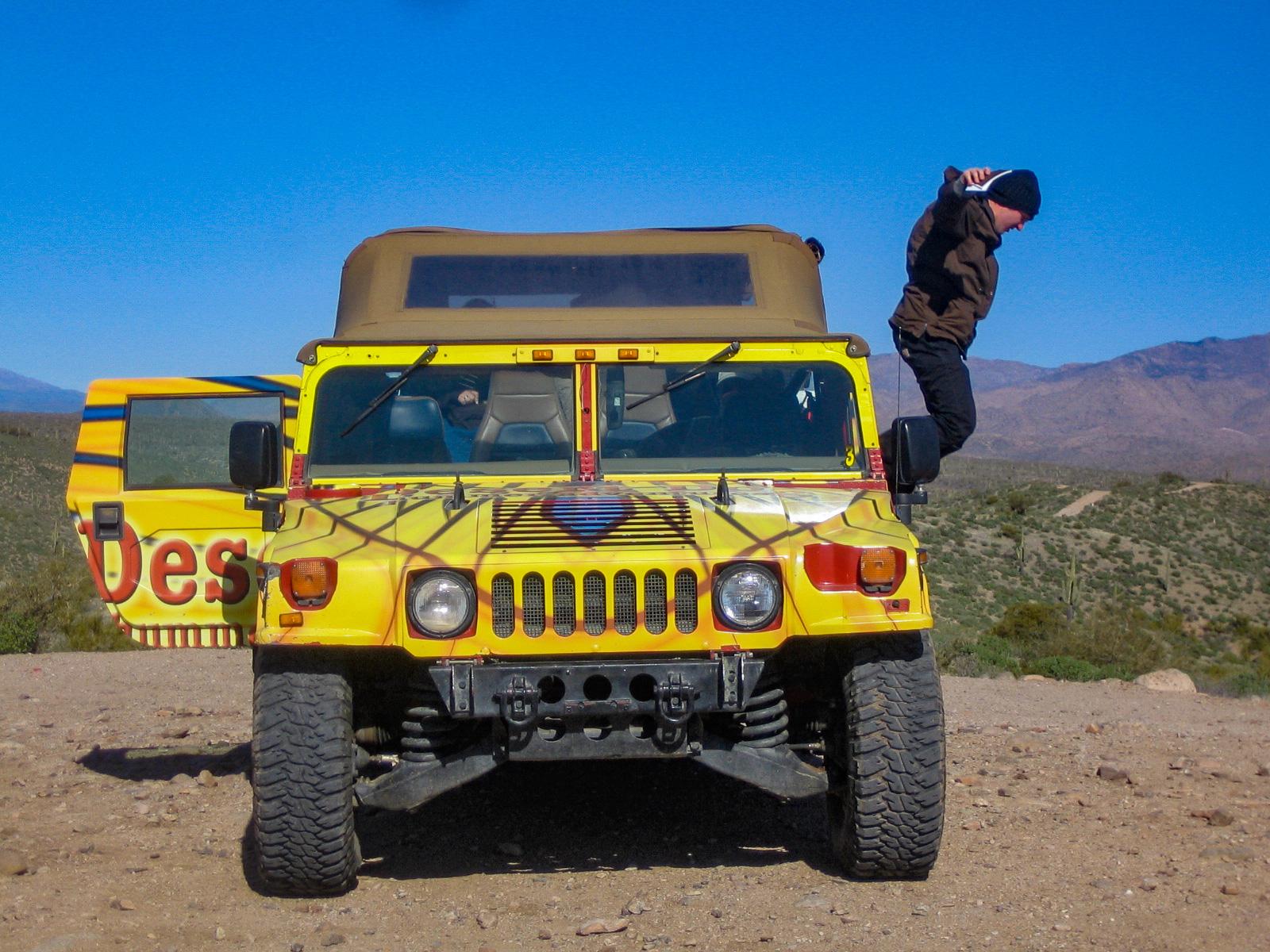 Ein Mann springt aus einem Hummer während einer Wüstentour bei Scottsdale