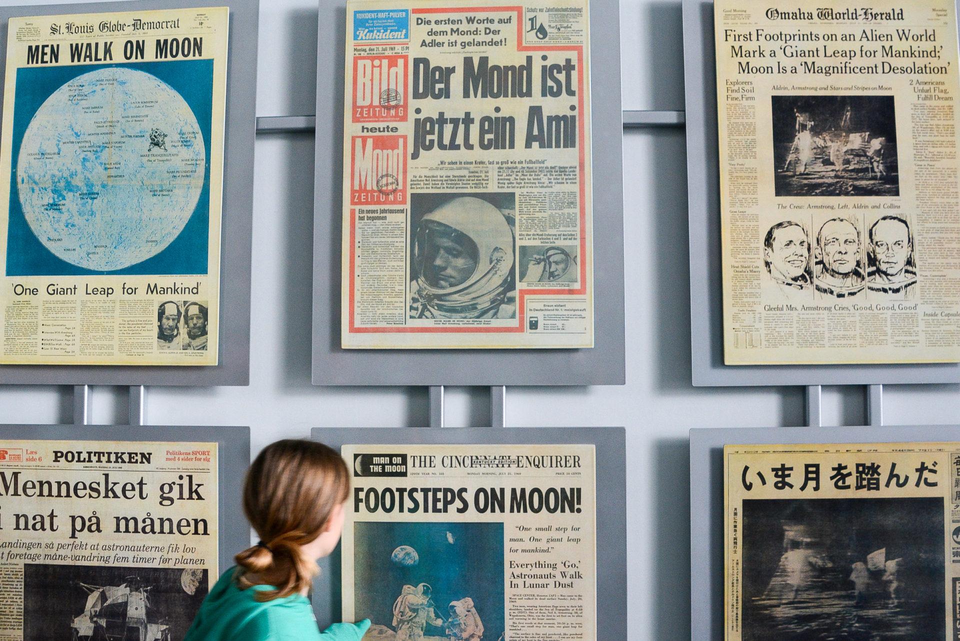 Kind staunt über Zeitungsausschnitte über Mondlandung im Kennedy Space Center in Florida