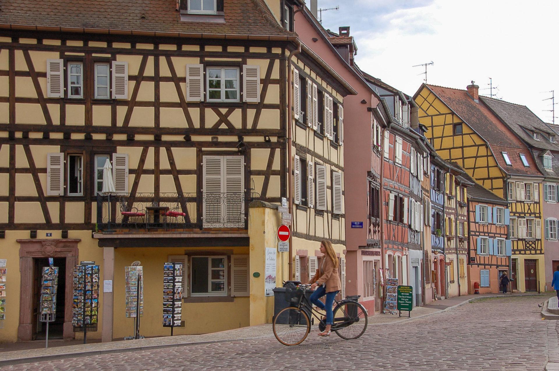 Frau auf Fahrrad vor Häusern mit Fachwerk in Colmar im Elsass