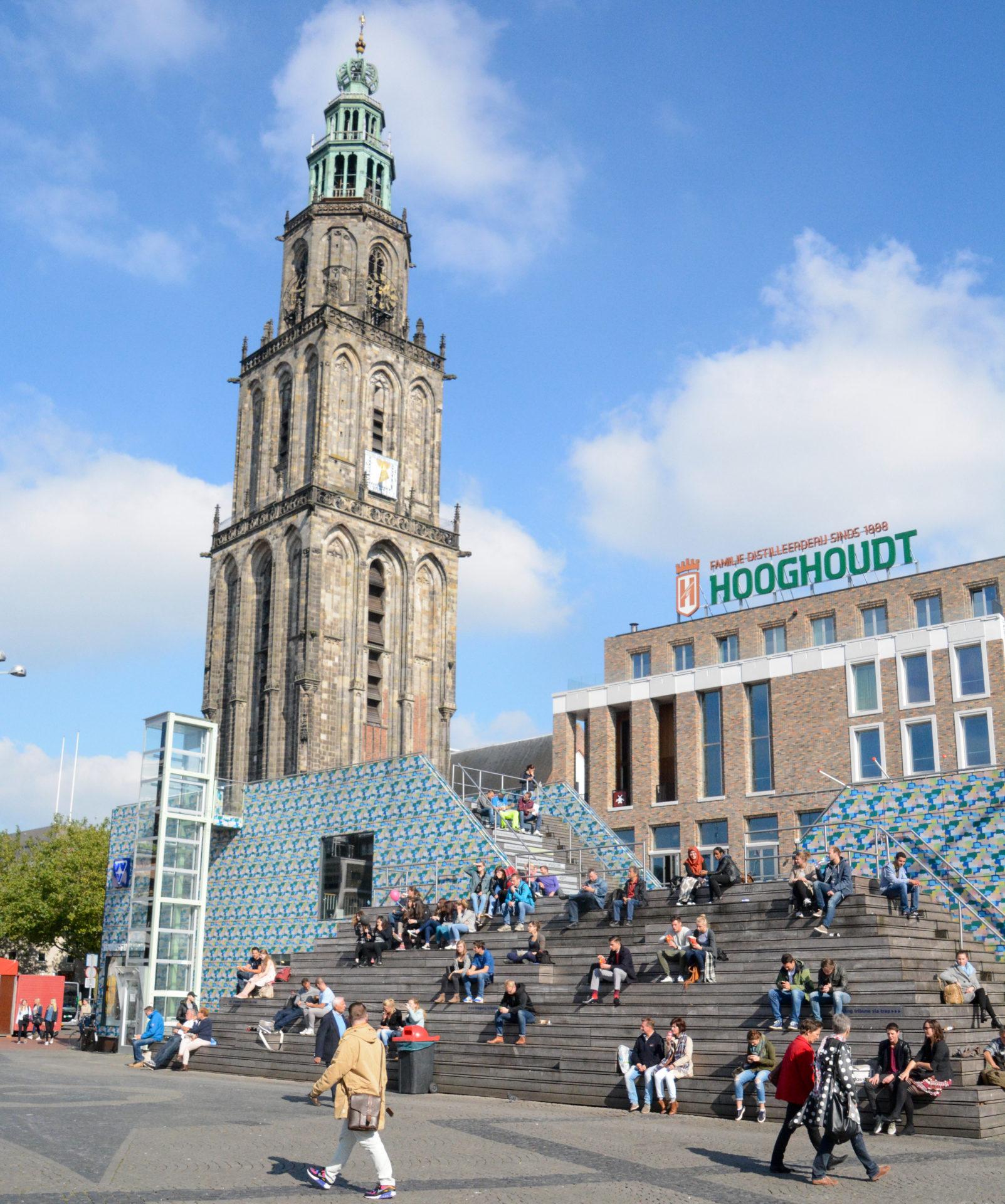 Die Martinikirche in Groningen mit Studenten auf einer Treppe
