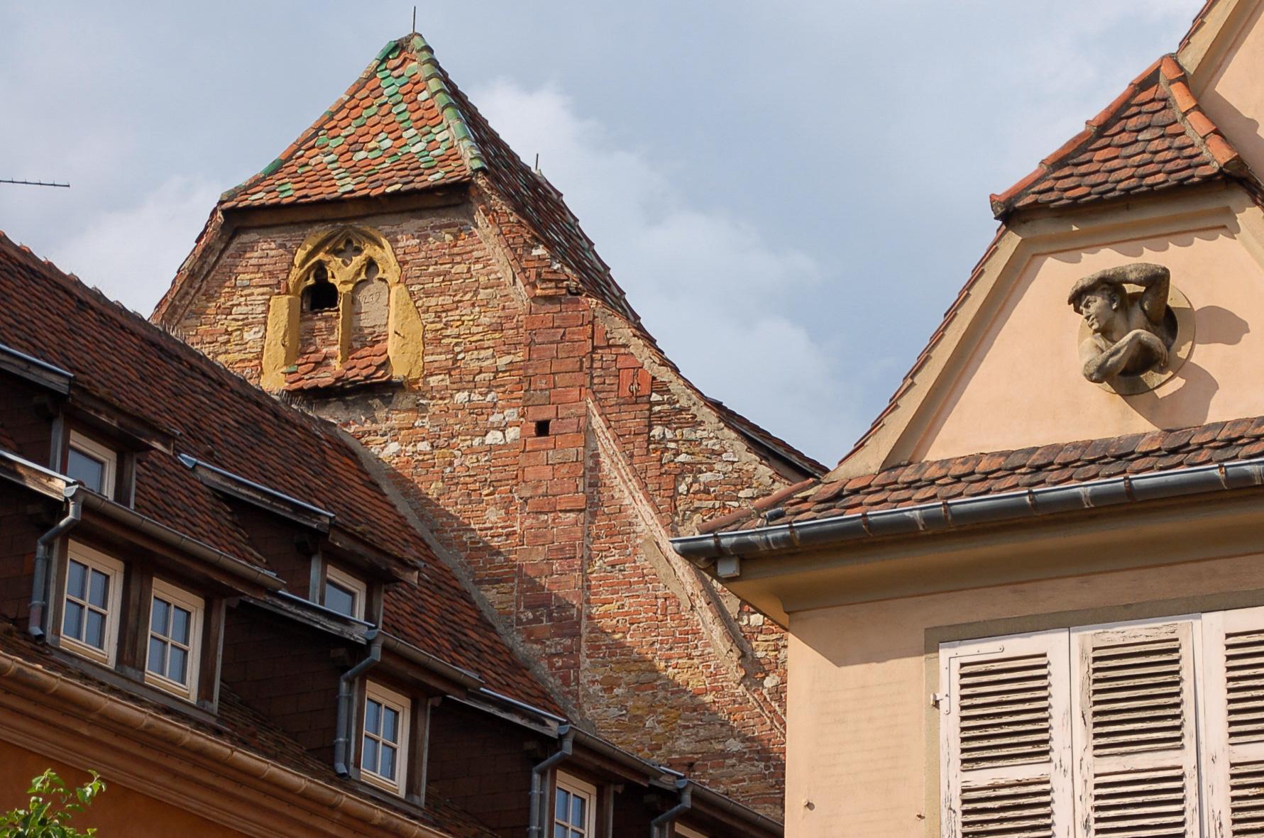 Eine Figur schaut aus einem Dachgiebel in Colmar