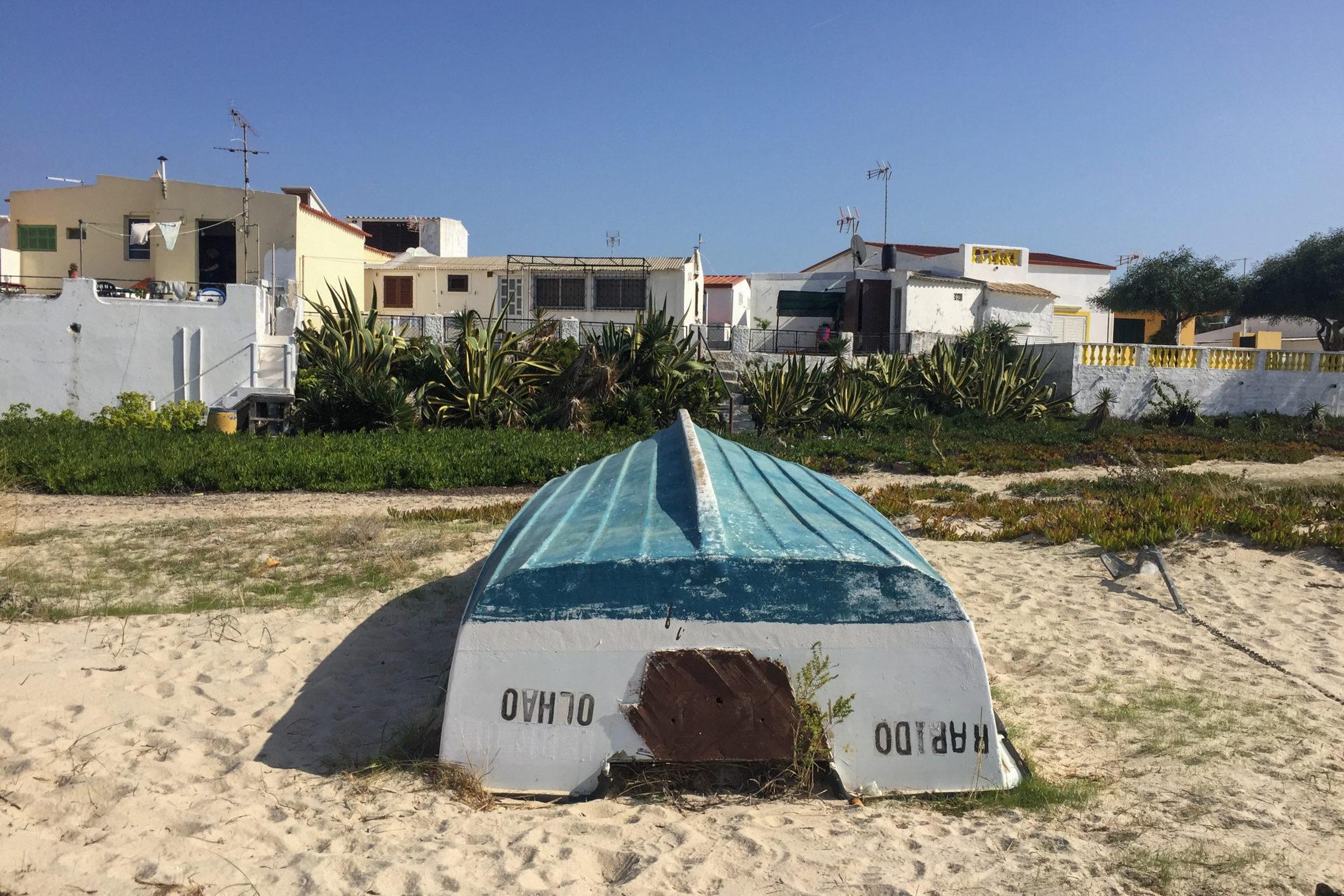 Umgedrehtes Boot am Strand der Ilha da Culatra mit Stranhäusern