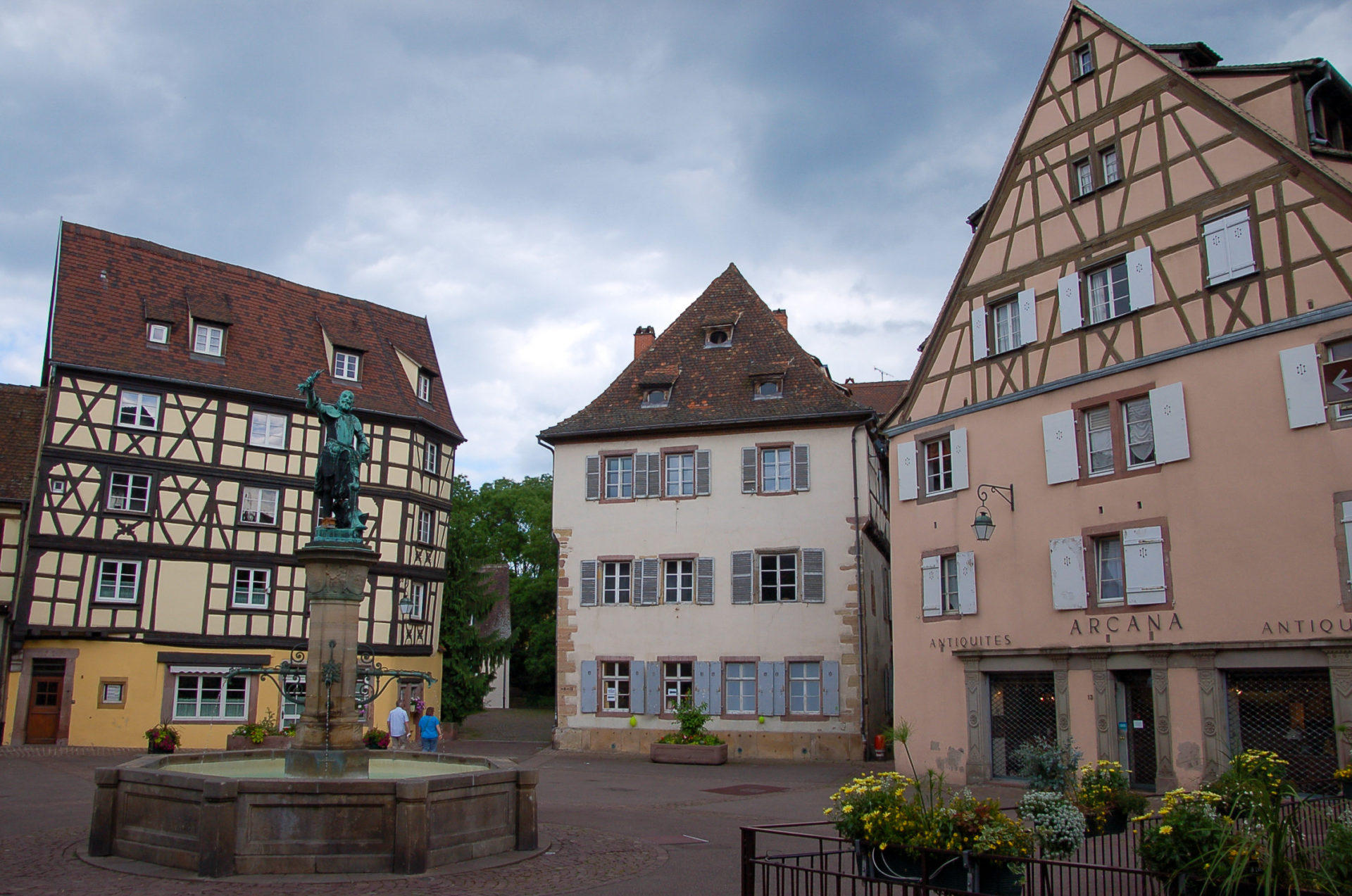 Springbrunnen mit Fachwerk in Colmar mit vielen Blumen