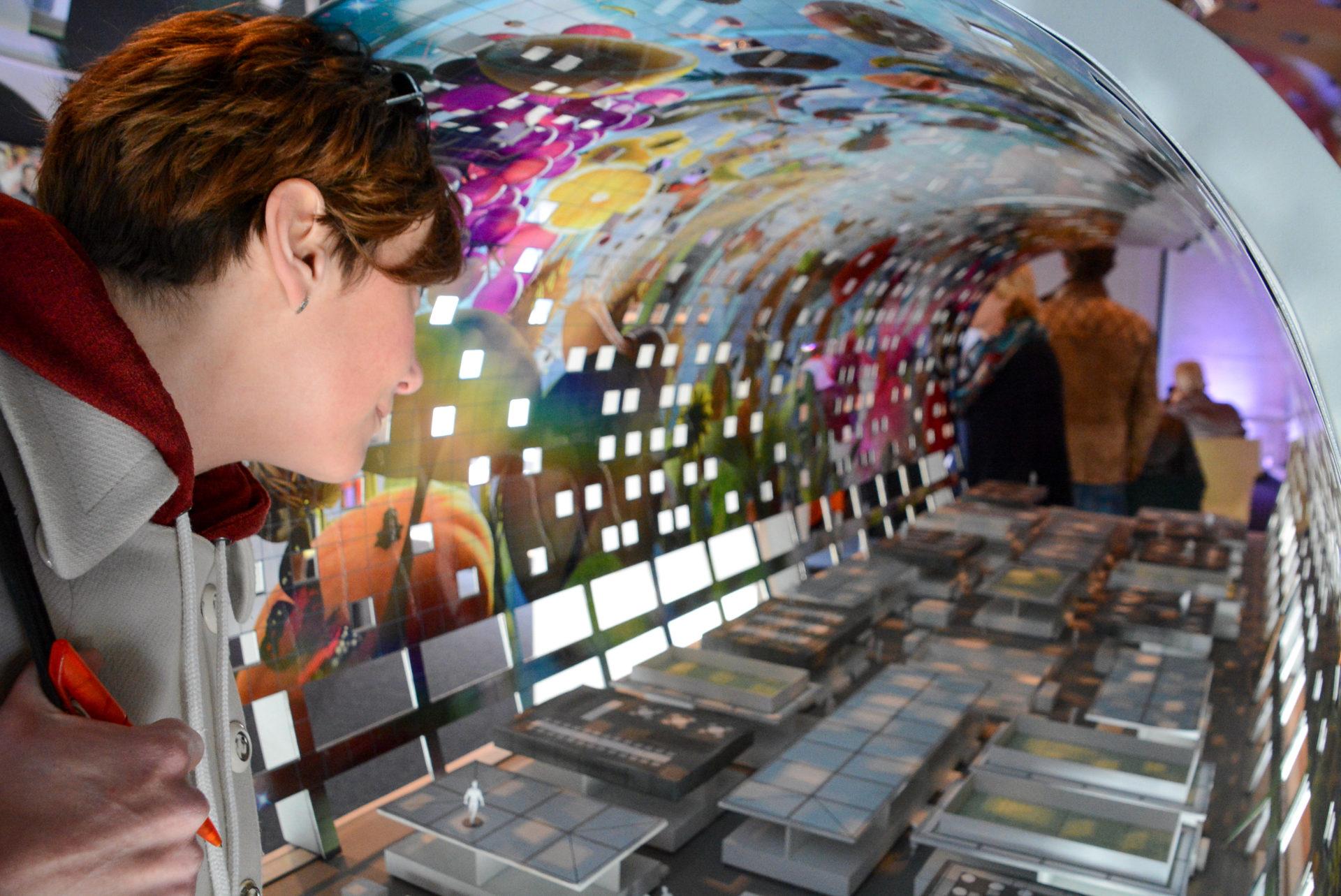 Model schaut auf ein Modell der Markthalle von Rotterdam