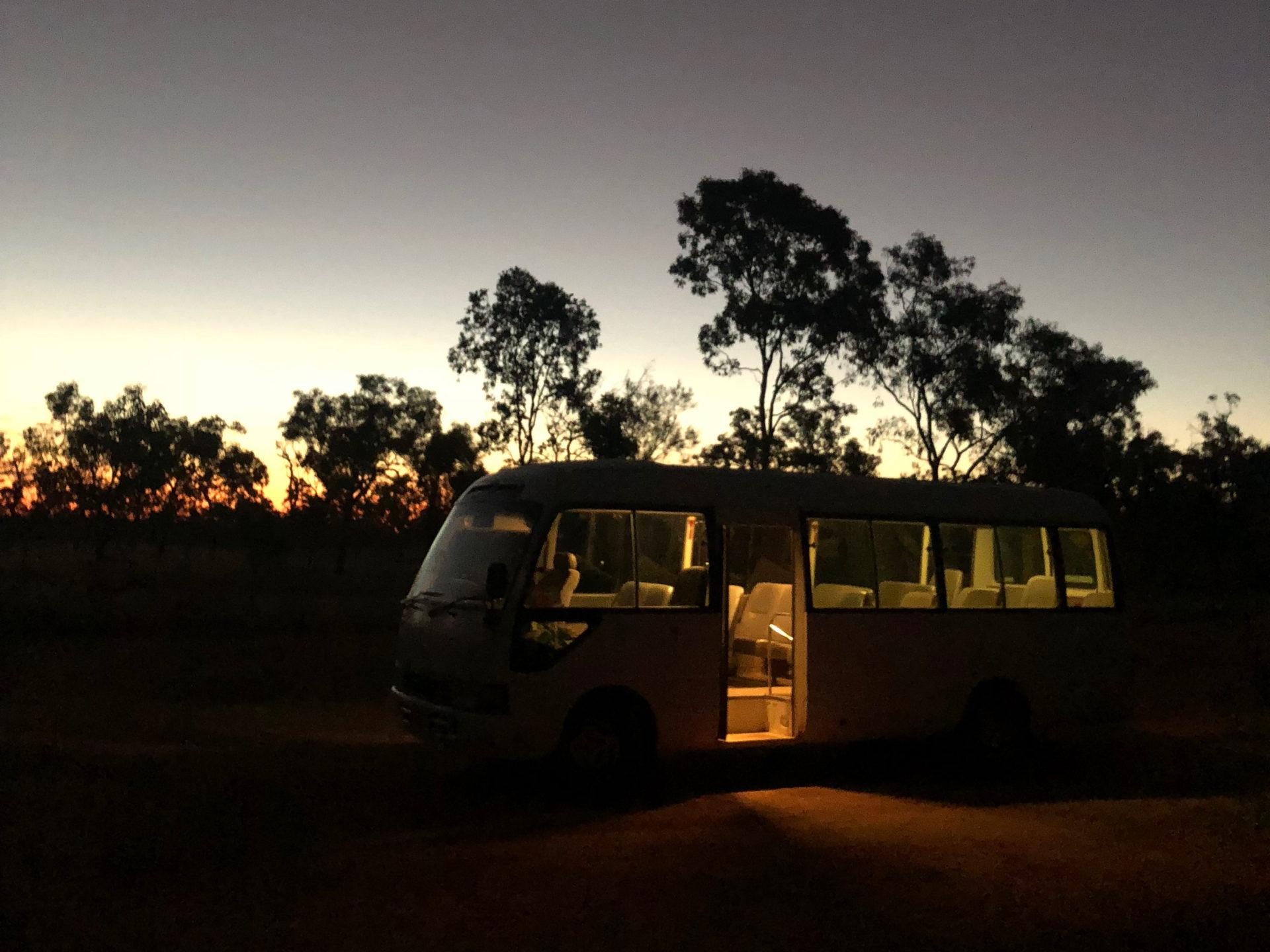 Leerer beleuchteter Bus auf einem Raod Trip durch Queensland vor der einbrechenden Dunkelheit und Eukalyptus-Bäumen in Queensland