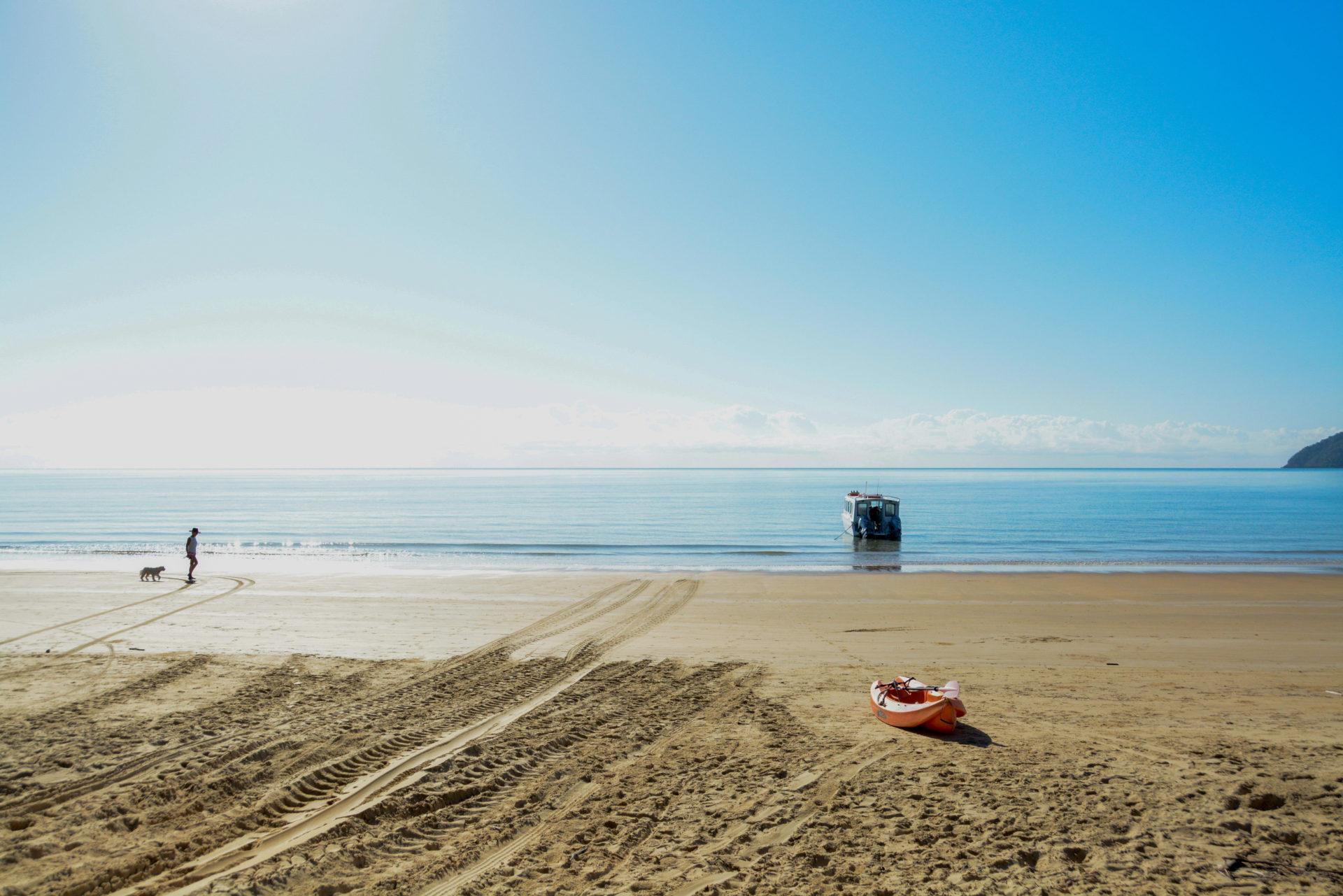 Mann mit Hund und Boot am spiegelglatten Pazifik in Etty Beach in Queensland