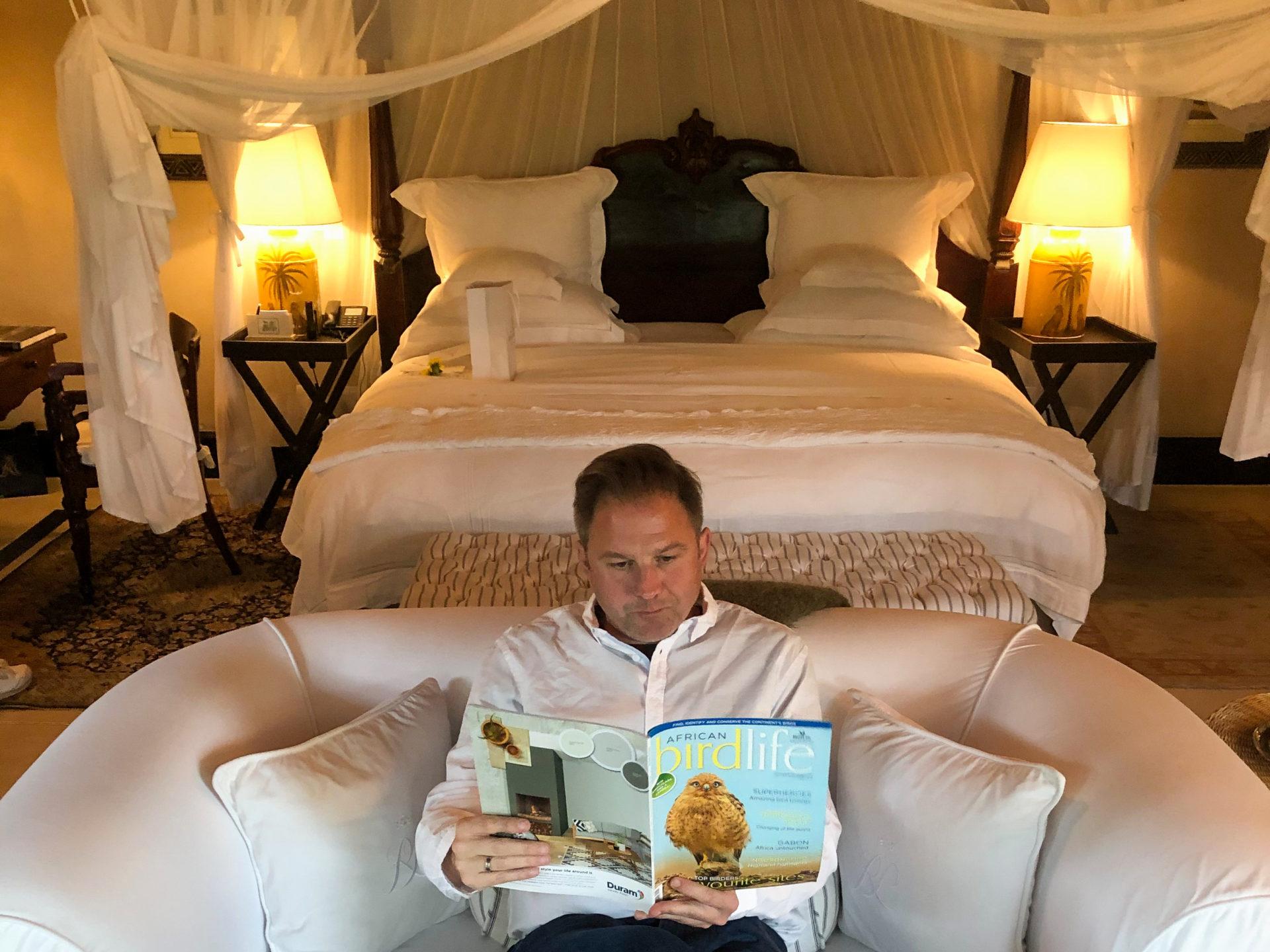 Autor vertieft in Magazin über afrikanische Vögel im Schlafzimmer des Royal Malewane.