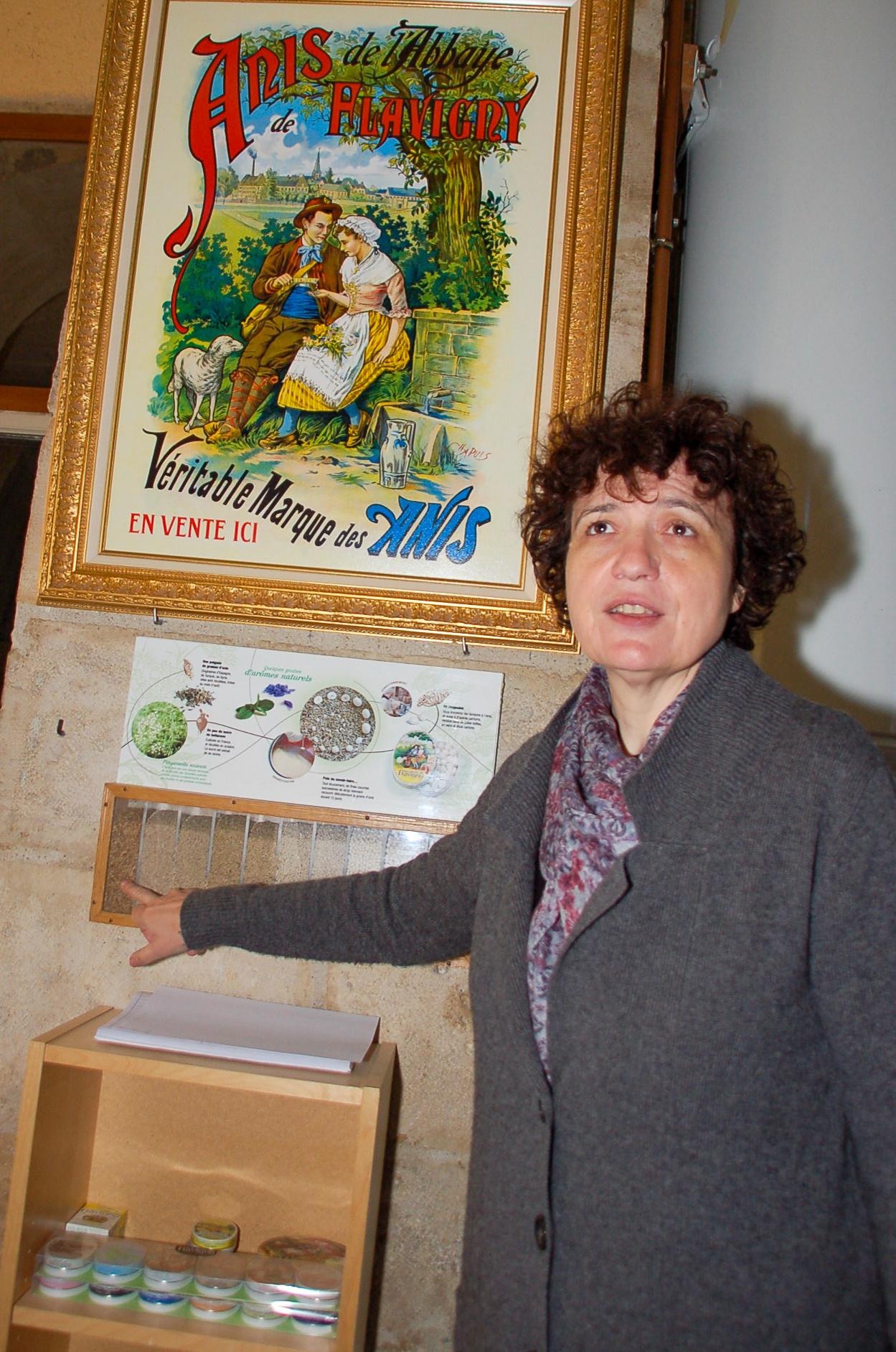 Catherine Troubat vor einem alten Firmenschild von Les Anis de Flavigny
