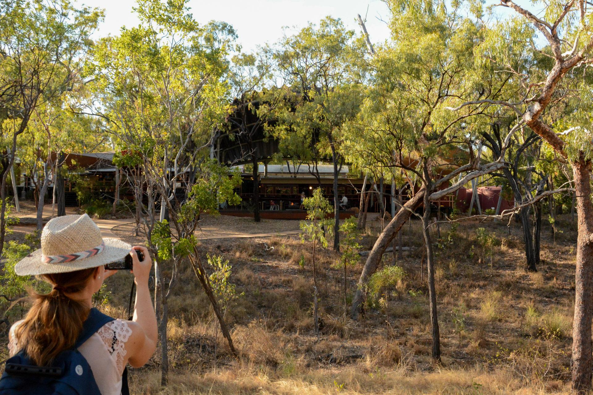 Frau mit Hut fotogragiert Eisenbahnwagon der Undara Experience während Road Trip durch Queensland