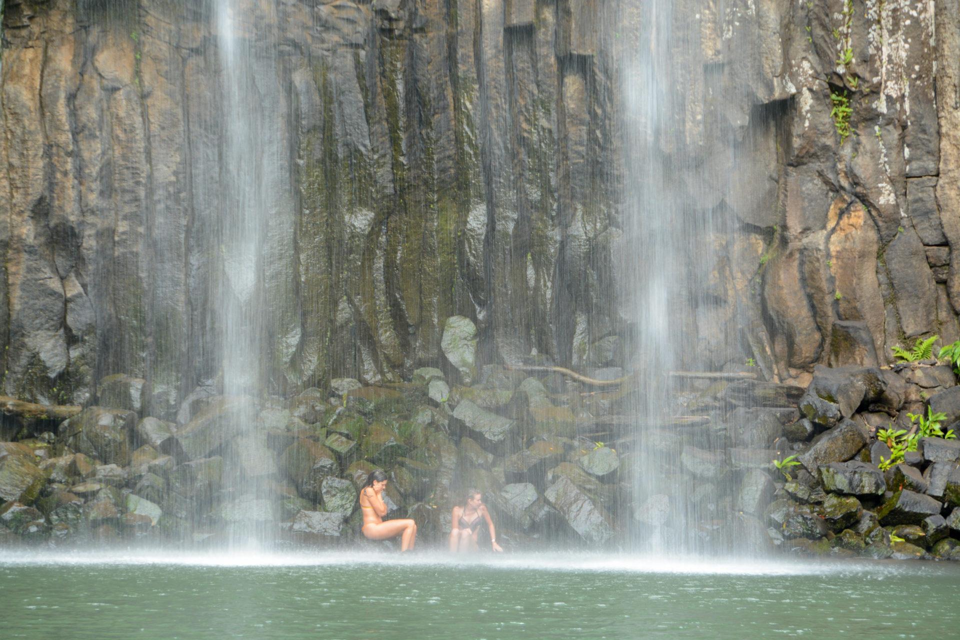 Zwei badende Mädchen an einem Wasserfall in Queensland in Australien